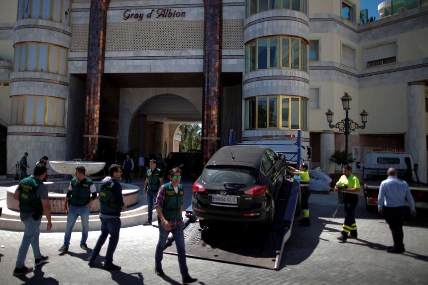 Officers confiscate a car outside the Gray D'Albion building at Puerto Banus in Marbella.