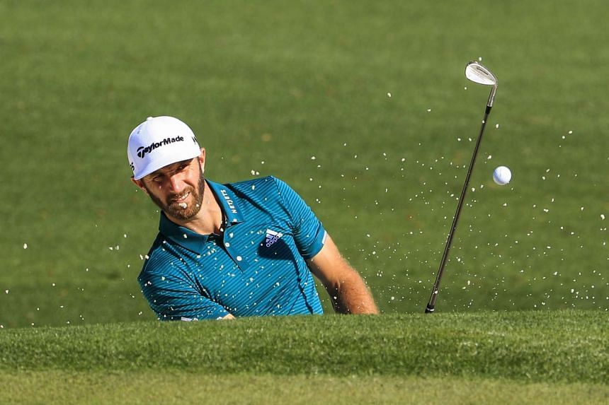 Dustin Johnson hits from a sand trap by the second green during a practice round at the 2017 Masters Tournament.