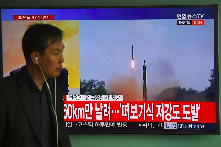 A man walks past a TV screen showing file footage of a North Korean missile launch, at a railway station in Seoul on April 5, 2017.