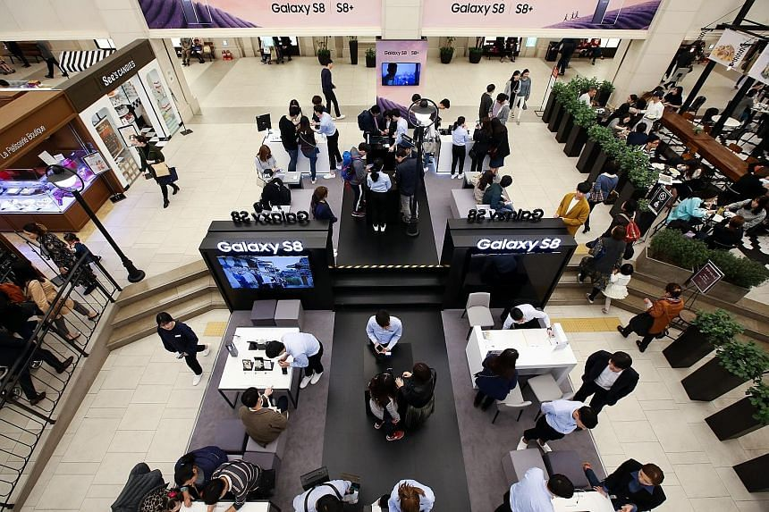 Visitors trying out the Galaxy S8 smartphones at one of the company's promotional booths in Seoul, South Korea, last weekend. The S8 features Bixby, Samsung's own AI-powered virtual assistant software, which sets the firm up in the AI race. The succe