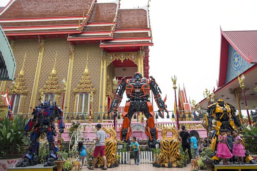 Thai children having fun with Transformer statues at Wat Takien temple in Nonthaburi province, Thailand, last Saturday. A Buddhist abbot decorated the temple with the statues, made from scrap metal, to inspire and attract children, young people and t