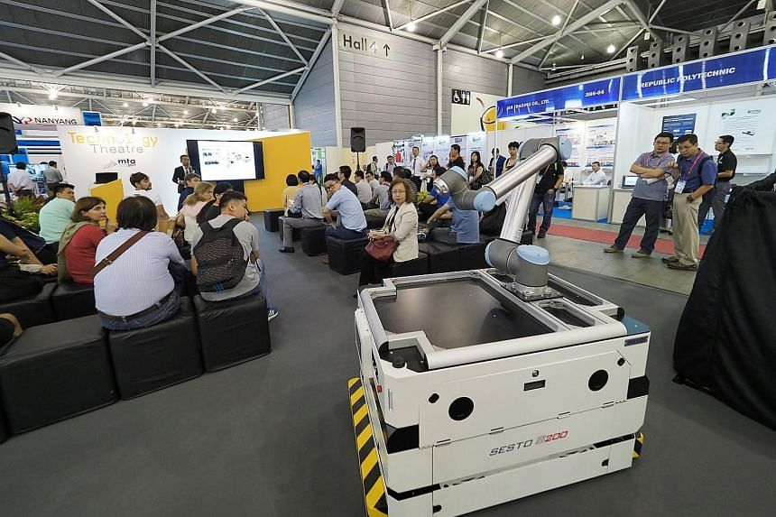 "Visitors interacting with technology provider ABB's ""collaborative robot"" (above), which slows or stops production when it senses operators around it for added safety. An automated guided vehicle by SESTO Robotics (below). Its intelligent software al"