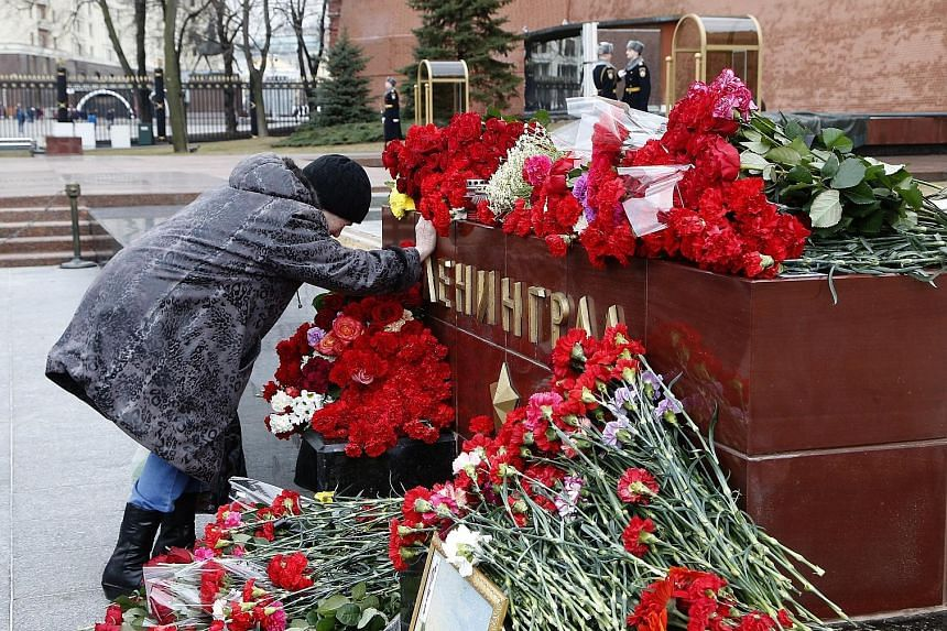 """Flowers were laid in memory of the victims of the St Petersburg metro blast at a memorial stone reading """"Leningrad"""" near the Kremlin wall in Moscow yesterday. Media reports said at least 14 people were killed and dozens hurt in the blast on Monday. R"""