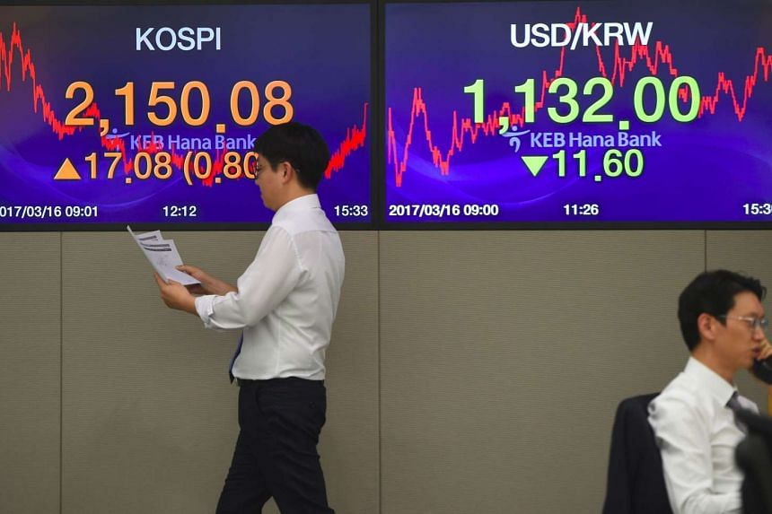 A currency dealer walking in front of screens showing South Korea's benchmark stock index (left) in a trading room at the KEB Hana Bank in Seoul, on March 16, 2017.