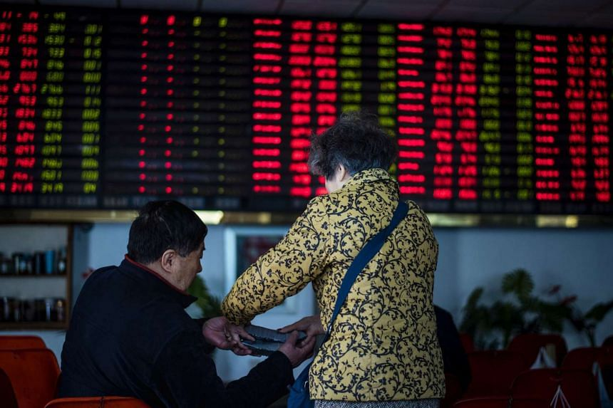 An investor (right) gives folded lucky money to a man next to an electronic board showing stock information at a brokerage house in Shanghai.