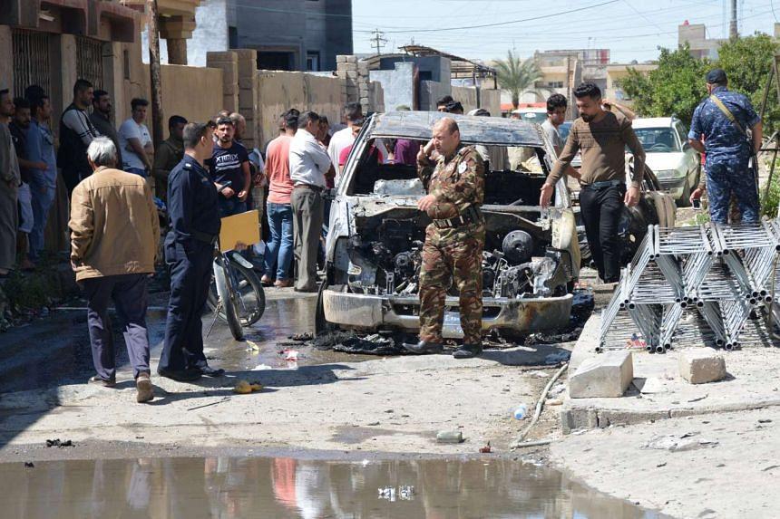 Locals and security forces walk near a burnt vehicle at the site of the attack in Tikrit.