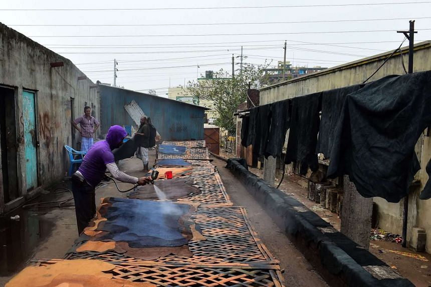 A Bangladeshi worker sprays coloured chemicals onto strips of leather.