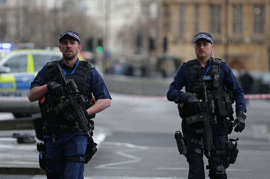 Armed British police officers patrol outside the Houses of Parliament in Westminster, London, on March 22, 2017.