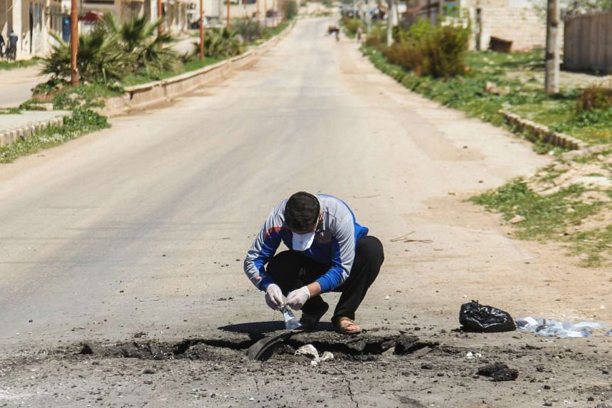 A Syrian man collects samples from the site of a suspected toxic gas attack in Khan Sheikhun, in Syria's northwestern Idlib province, on April 5, 2017.