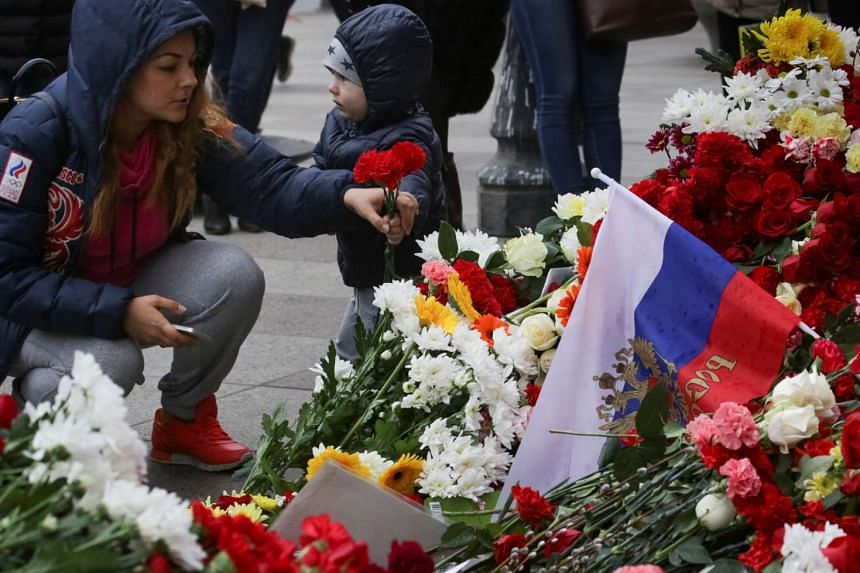 A woman places flowers at a memorial site for the victims of the St Petersburg attack.