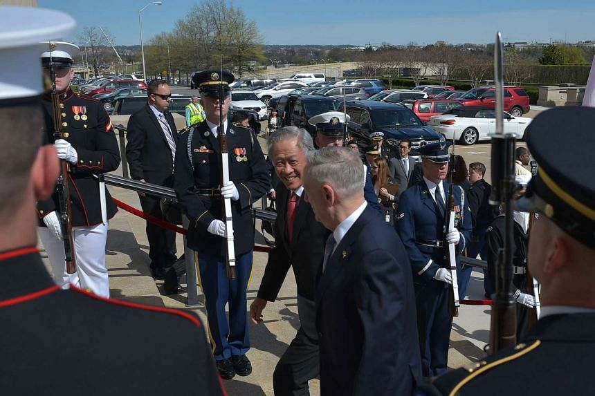US Defence Secretary James Mattis escorts Singapore's Defence Minister Ng Eng Hen as he arrives at the Pentagon for meetings on April 5, 2017, in Washington, DC.