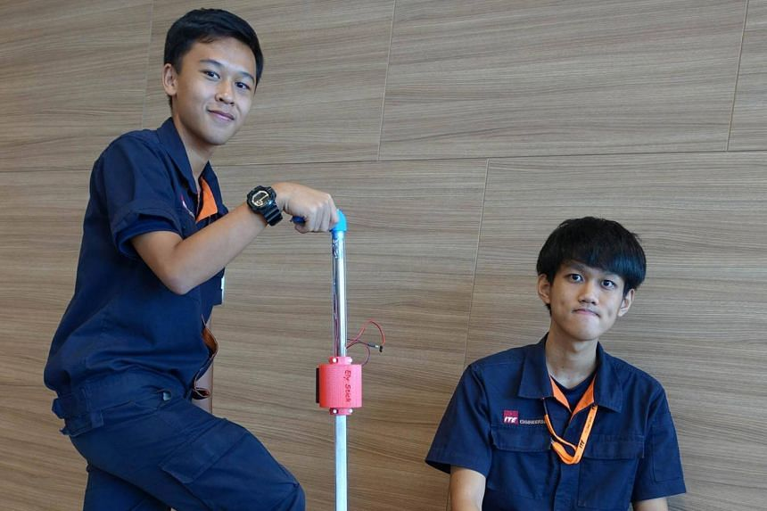 Chua Yi Xiang (left) and Jenson Ting Kian Seng, both 17, pose with their invention the Ely Walking Stick.