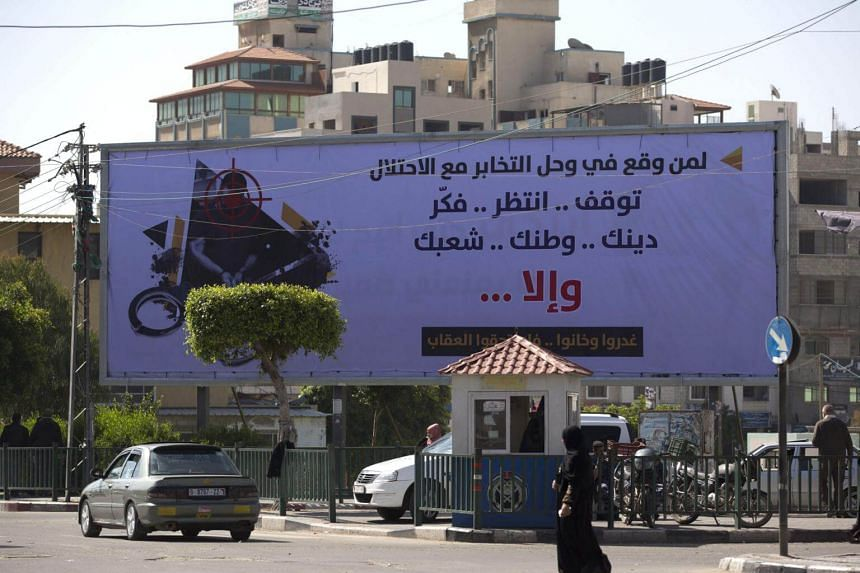 """A banner in Gaza City which says in Arabic: """"For those who fell into the trap of collaboration with the occupation. Stop, hold on and consider your religion, your homeland, your people...or else..."""""""