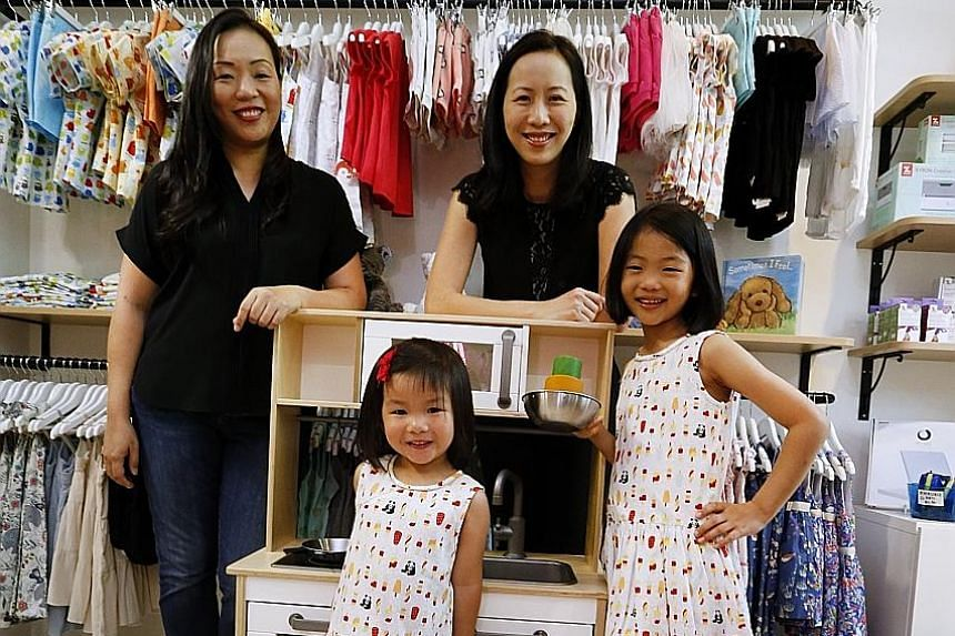 Sisters Carol (far left) and Audrey Ng, founders of children's label Elly, at their store in Cluny Court. With them are Carol's daughters Sophie, seven, and Emelie, three.