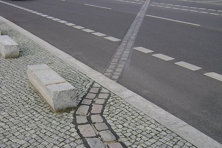 Cobblestone markers that indicate where the Berlin Wall once stood. A writer suggests that something similar be done in Singapore to show where the original shoreline was before land reclamation.
