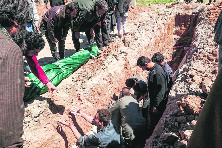 Many Syrians spent yesterday burying and mourning the victims of Tuesday's chemical weapons attack, which caused scores of people to choke to death, including 20 children, and left a hospital in chaos. People getting medical aid on Tuesday after the