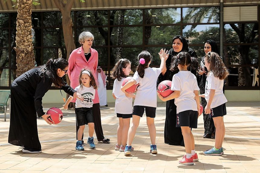 British Prime Minister Theresa May with Saudi Princess Reema bint Bandar Al Saud (seen here high-fiving a pupil) during a visit to the General Sports Authority's Leadership Institute in Riyadh, Saudi Arabia, yesterday.