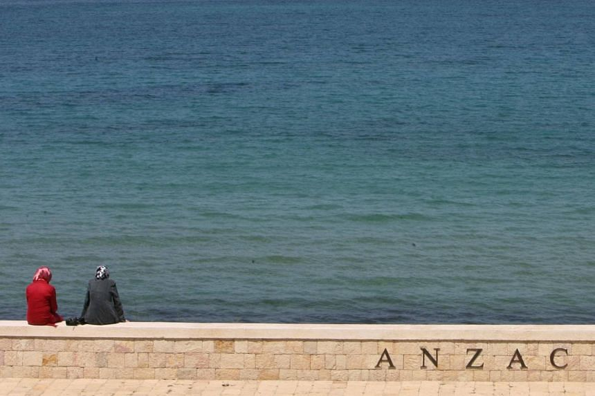 Tourists sit at Anzac Cove where the first battle was fought in Gallipoli.