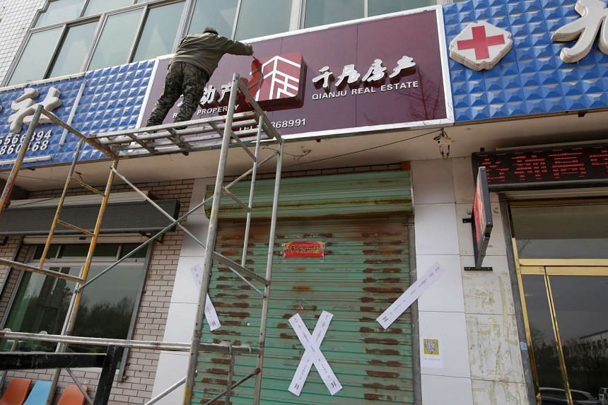 A worker removing the logo of a closed real estate agency after the government banned property sales in counties earmarked as part of a new special economic zone in Xiongxian county, Hebei province, China, on April 3, 2017.