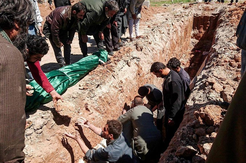 Syrians digging a grave to bury the bodies of victims of a a suspected toxic gas attack in Khan Sheikhun, a nearby rebel-held town in Syria's northwestern Idlib province, on April 5, 2017.