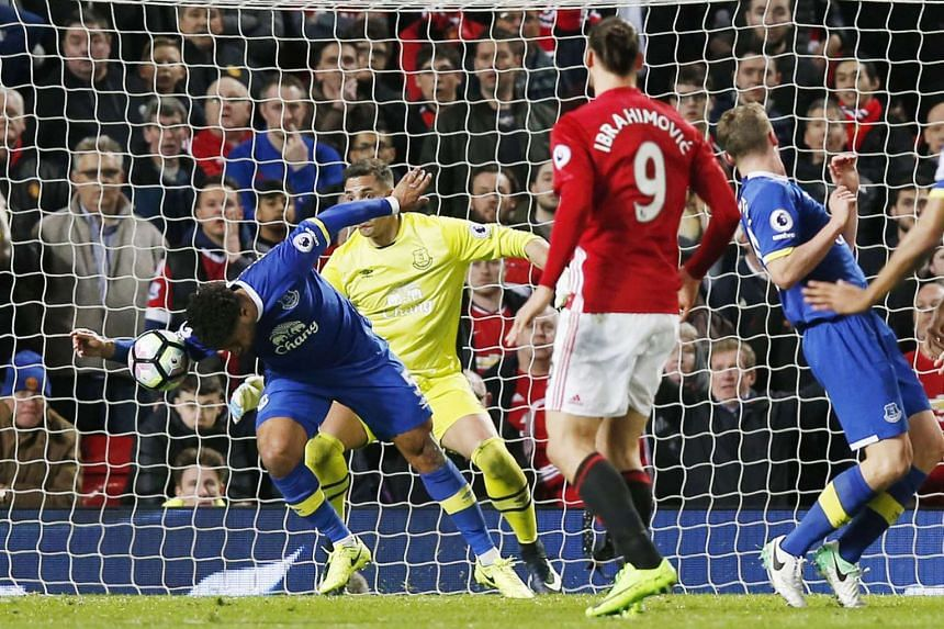Everton defender Ashley Williams handles the ball in the box after a shot by United's Luke Shaw in an English Premier League match at Old Trafford. Williams was sent off before Zlatan Ibrahimovic converted a stoppage-time penalty to make it 1-1.