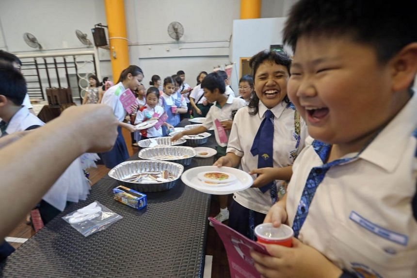 South View Primary School pupils Ethan Ang, 11, and Siti Syazwana, 11, take food from a simulated buffet at Chongzheng Primary School. Students were guided through a food waste educational trail set up at the school by the NEA.