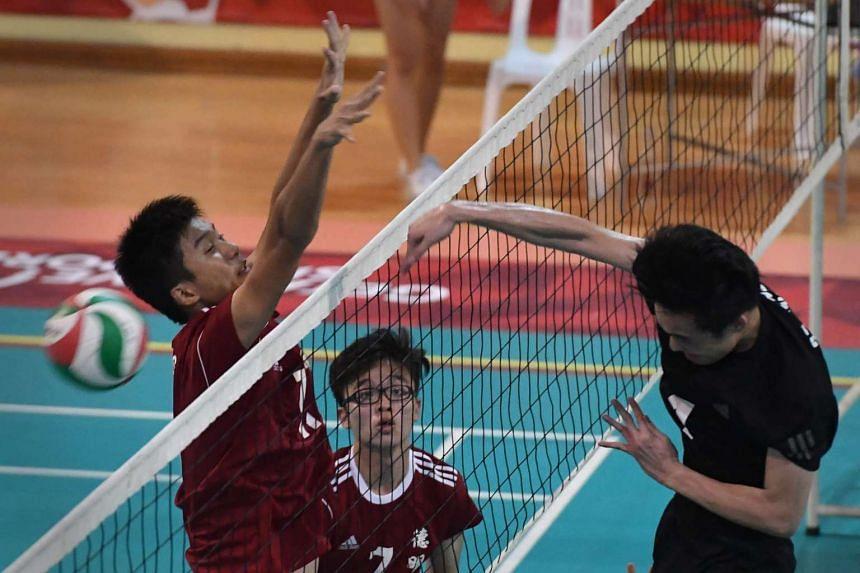 St. Hilda's Sean Lee Jian Hao (right) smashing the ball past Dunman's Zhang Zhenhao.
