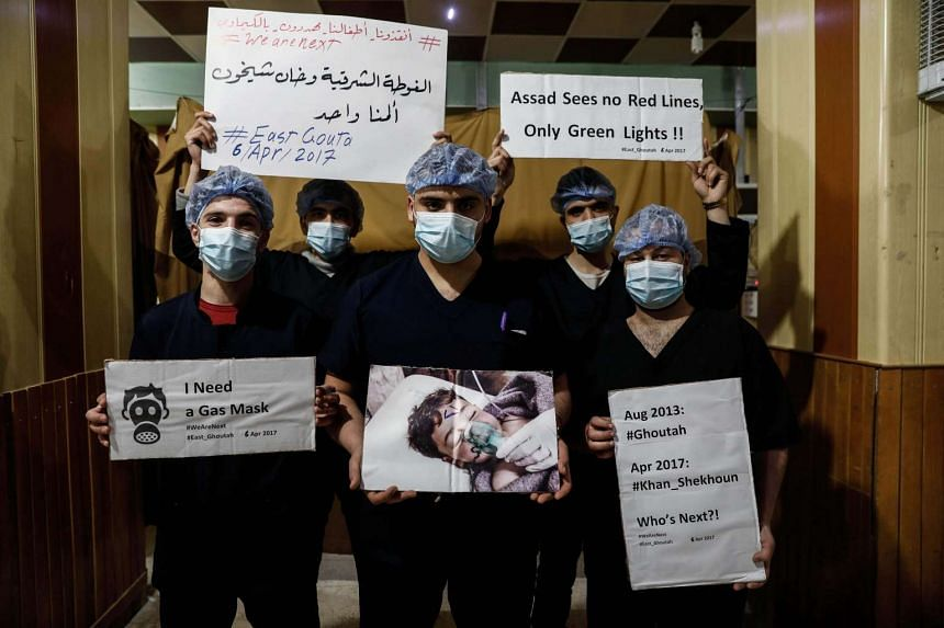 Medical staff at Damascus Countryside Specialised Hospital hold placards condemning a suspected chemical weapons attack on the Syrian town of Khan Sheikhun on April 6, 2017.