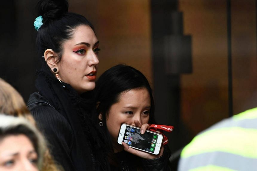 People react at the scene where a truck crashed into the Ahlens department store at Drottninggatan in central Stockholm on April 7, 2017.