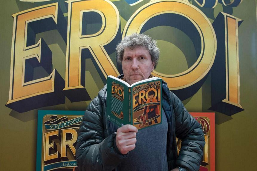 Italian writer Antonio Ferrara poses with his book Semplicemente Eroi (Simply heroes) during the International Children's book fair on April 5, 2017 in Bologne.