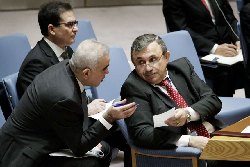Mounzer Mounzer (right), Syria's Deputy Ambassador to the United Nations, talks to an aide duing an emergency meeting of the United Nations Security Council about a chemical attack in Syria at United Nations headquarters in New York.