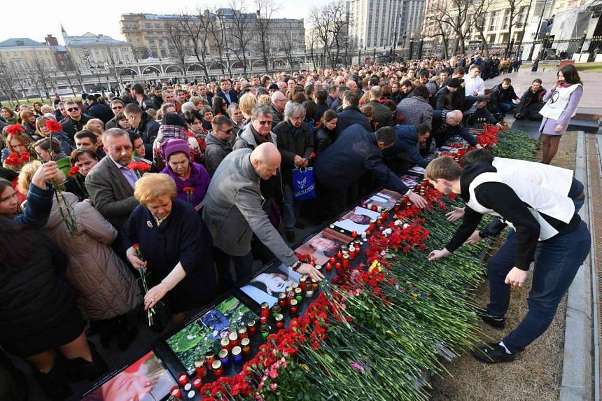 People place flowers in honour of the victims during a commemorative event in central Moscow on April 6, 2017.