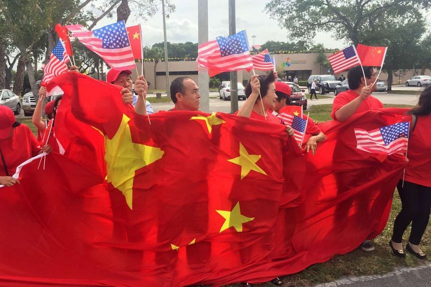 China supporters wave Chinese and US flags as they wait for the arrival of China's President at Palm Beach international airport on April 6 2017.