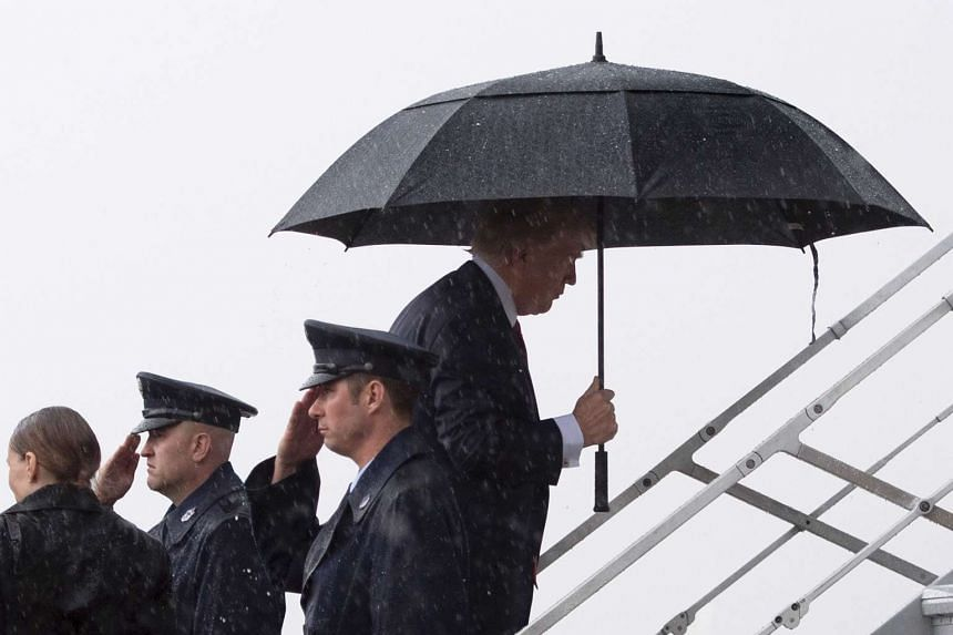 Trump (third right) boards Air Force One under heavy rain at Andrews Air Force Base, Maryland, April 6, 2017.