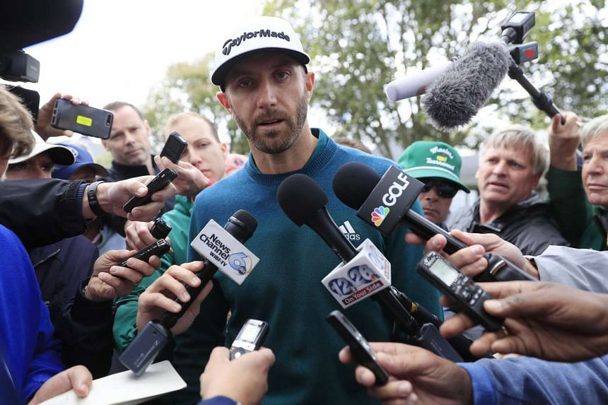 Dustin Johnson of the US speaks with the media outside the clubhouse after withdrawing from the Masters due to injury just as he reached his tee time for the first round.