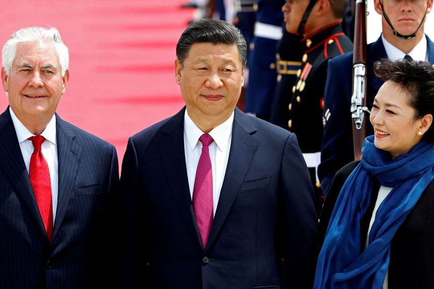 US Secretary of State Rex Tillerson (left) stands with China's President Xi Jinping and his wife, Peng Liyuan.