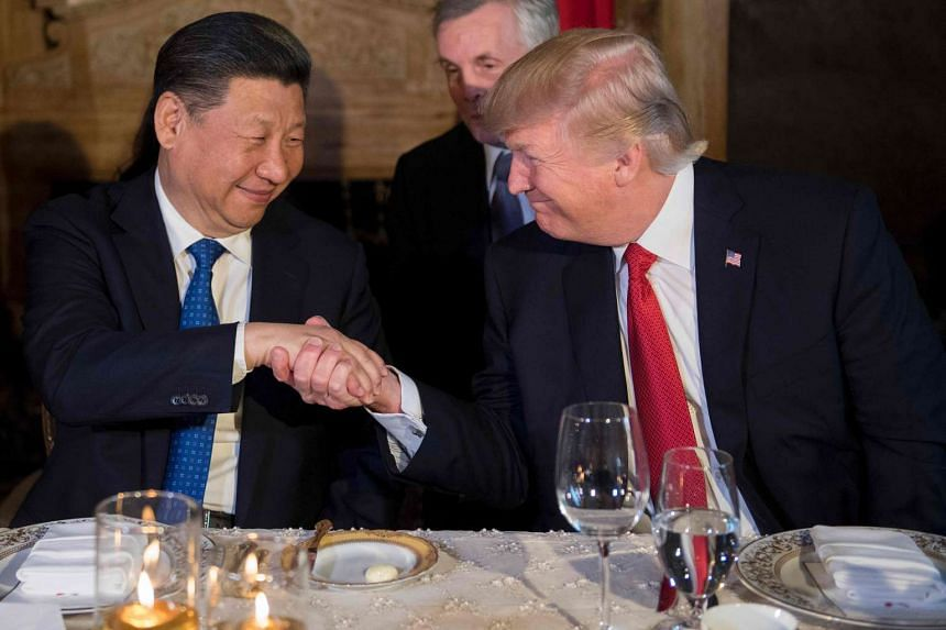 US President Donald Trump (right) and Chinese President Xi Jinping shake hands during dinner at the Mar-a-Lago estate in West Palm Beach, Florida, on April 6, 2017.