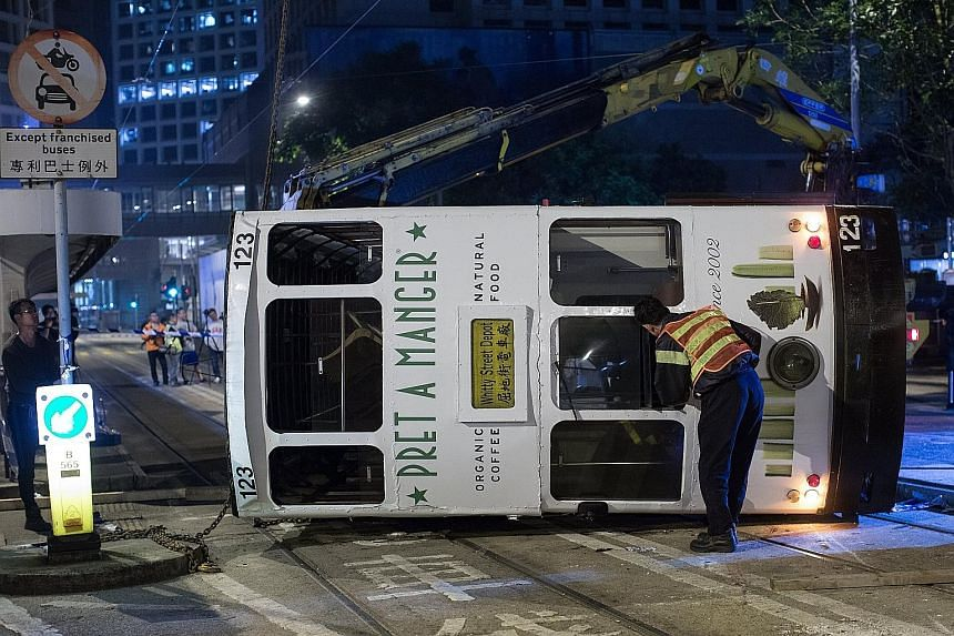 The double- decker tram tipped over in Hong Kong's Central District at around midnight yesterday. Five women and nine men, including the driver, were injured. He was later arrested for dangerous driving. The accident is rare for the city's highly eff
