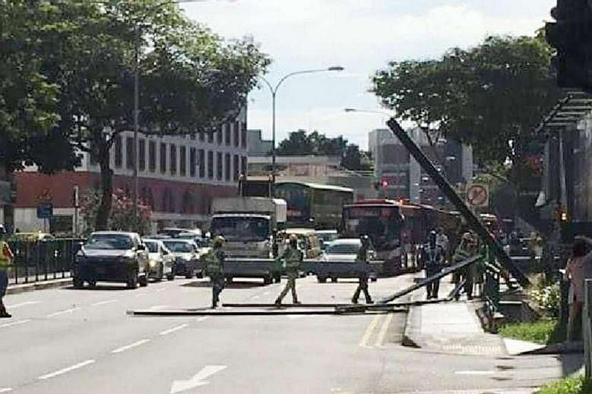 Workers from the Viio@Balestier site removing the fallen metal beams from Balestier Road. The beams, which narrowly missed pedestrians and vehicles, made holes on the road and damaged a barrier.