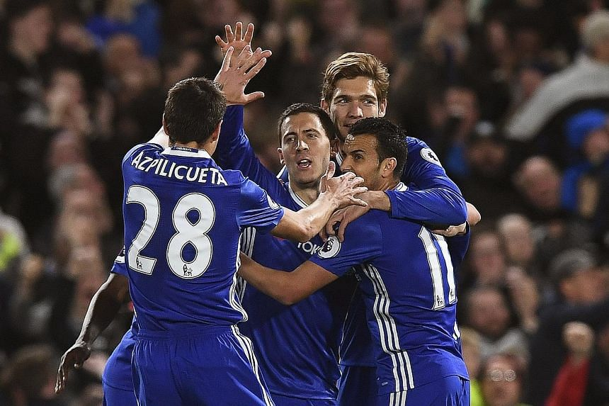 Above: Chelsea forward Eden Hazard (centre) celebrates after scoring against Manchester City. The Belgian recorded his 12th and 13th goals of the season on Wednesday.
