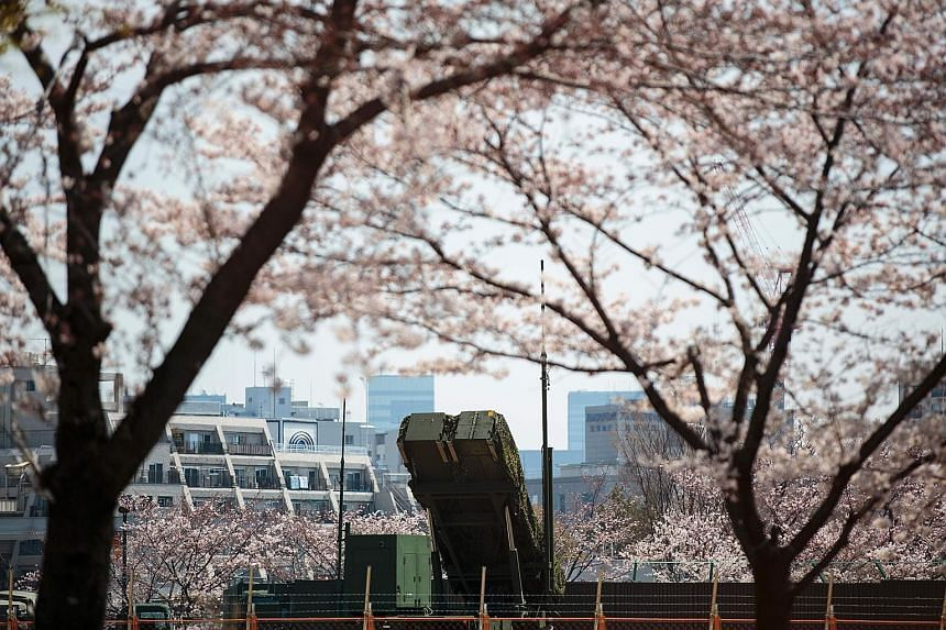 A PAC-3 surface-to-air missile launcher unit, used to engage incoming ballistic missile threats, seen through cherry blossoms at the Defence Ministry in Tokyo on Wednesday.