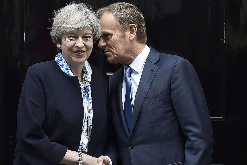 British Prime Minister Theresa May greeting EU President Donald Tusk outside Downing Street yesterday. The EU has rejected Mrs May's call for talks on terms of the divorce and a future trade deal to be held in parallel during the two years of negotia