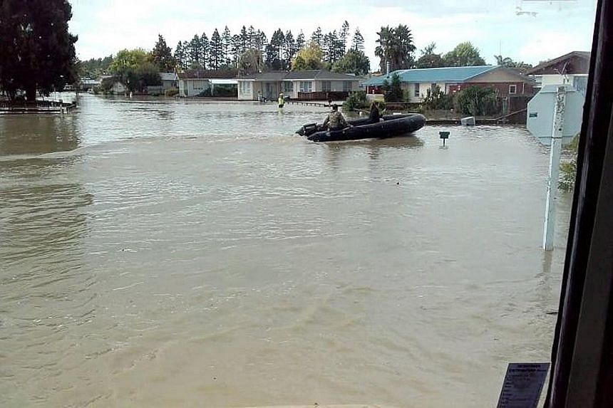 "New Zealand Defence Force personnel at work in the flood-stricken town of Edgecumbe on the North Island yesterday. No deaths have been reported in New Zealand, but ""there's still a risk of loss of life"", Deputy Prime Minister Paula Bennett said amid"