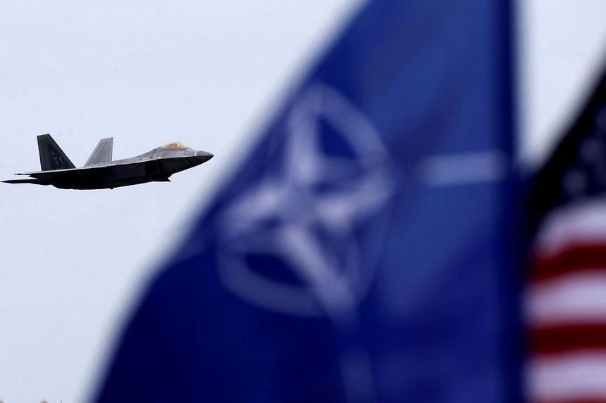 NATO and US flags flutter as US Air Force F-22 Raptor fighter flies over the military air base in Siauliai, Lithuania.