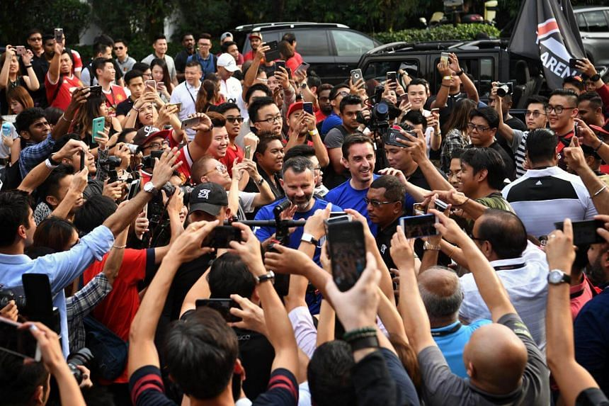 Manchester United legends Ryan Giggs (left) and Gary Neville are mobbed by fans before the opening ceremony of The Arena and Cafe Football at Woodleigh Park on April 8, 2017.