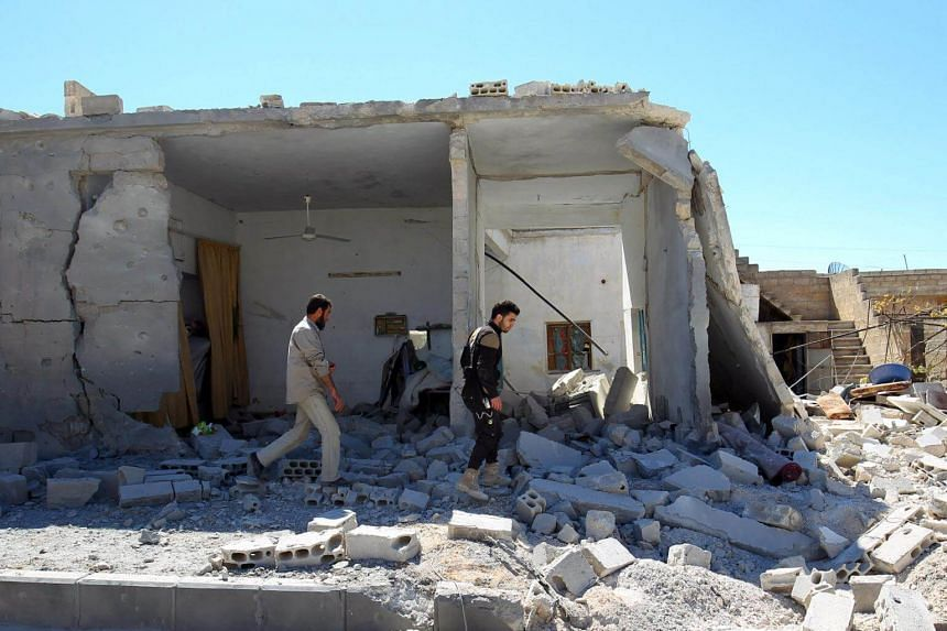Civil defense members inspect the damage at a site hit by airstrikes, in the town of Khan Sheikhoun in rebel-held Idlib, Syria, on April 5, 2017.
