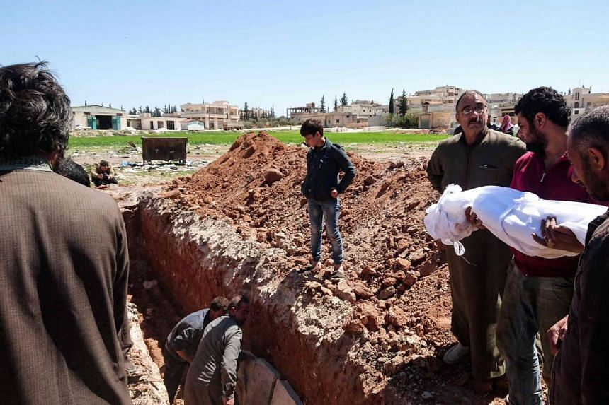 Syrians bury the bodies of victims of a suspected toxic gas attack in Khan Sheikhun, a nearby rebel-held town in Syria's north-western Idlib province, on April 5, 2017.