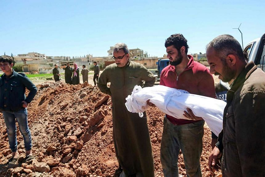 Syrians bury the bodies of victims of a suspected toxic gas attack in Khan Sheikhun, a nearby rebel-held town in Syria's northwestern Idlib province, on April 5, 2017.