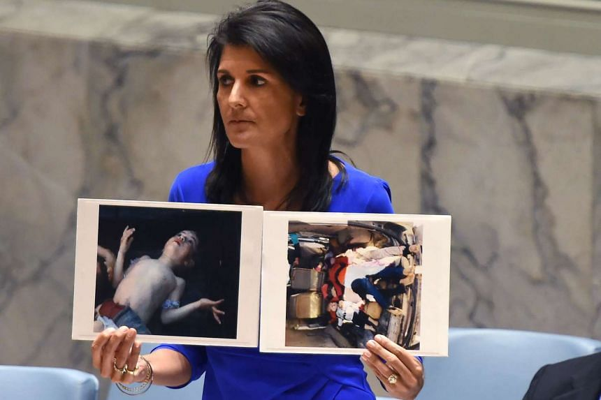 US Ambassador to the UN, Nikki Haley, holds photos of victims as she speaks at the UN Security Council emergency session at the UN on April 5, 2017.