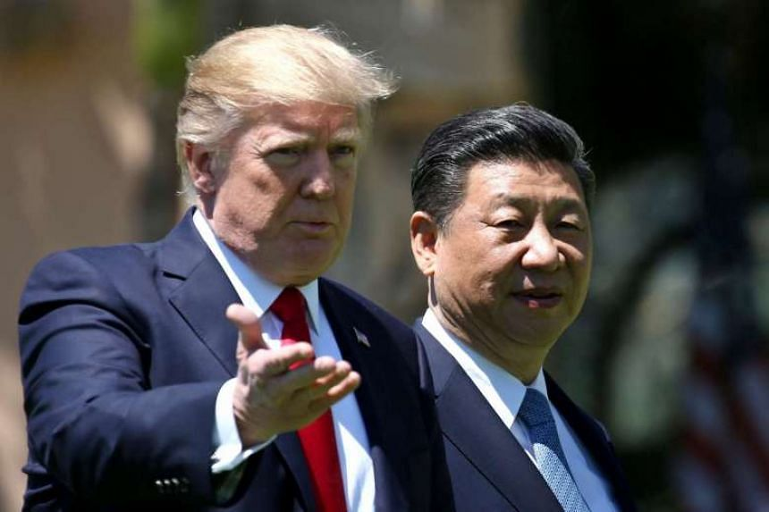 US President Donald Trump and China's President Xi Jinping chat as they walk along the front patio of the Mar-a-Lago estate after a bilateral meeting.